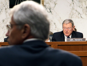 Sen. Jim Inhofe, ranking member of Senate Armed Services Committee, and Secretary of Defense Chuck Hagel look at a chart Inhofe reference during a committee hearing. The chart shows President Obama's plans to fund defense spending at 16 percent of the federal budget compared to President Reagan's federal budget in 1989 that funded defense at 28 percent.