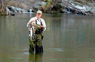 An angler holds up his stringer after adding another rainbow trout at the Blue River Public Fishing and Hunting Area. (Photo by wildlifedepartment.com)