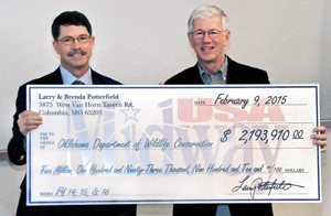 Richard Hatcher, director of the Oklahoma Department of Wildlife Conservation, and Larry Potterfield, founder of MidwayUSA Inc., hold a symbolic check for more than $2.1 million, representing the total money donated over three years by MidwayUSA Foundation and the Potterfield family for the Oklahoma Scholastic Shooting Sports Program.