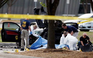 FBI crime scene investigators document the area around two deceased gunmen and their vehicle outside the Curtis Culwell Center in Garland, Texas, Monday
