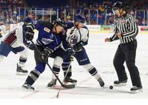 Phil Brewer (white jersey) battles a Wichita Thunder player after a faceoff.