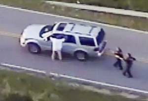 Crutcher and police (Photo frame capture from helicopter video)
