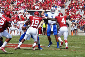 TU quarterback Cody Green looks too pass while OU's Hatari Byrd and Eric Striker close in in 2013.
