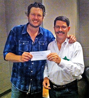 Country music star Blake Shelton hands a check for $20,000 to Richard Hatcher, director of the Wildlife Department after an Oct. 4 concert in Tulsa. Shelton donated the money to the Wildlife Department to support the agency's suite of outdoor education programs