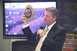 "Costello holds logo promoting ""Workers Comp Not Lawyers Comp"""