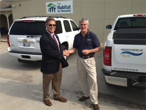Apache Corporation Executive Vice President Rob Johnston, left, presented Tulsa Habitat for Humanity Executive Director Paul Kent with the keys to a pickup truck powered by compressed natural gas.