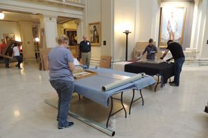 Sen. Charles Ford watches as Senate art is prepared for transport