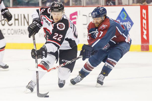 Kale Kerbashian (22) battles the Oilers Jon Booras (27) for the puck in Thursday night's game. Photo: Kevin Pyle