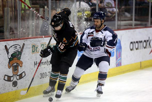 A battle along the boards ensues between Justin Fox (dark jersey) and Dave Pszenyczny in Quad City. Photo: Oilers